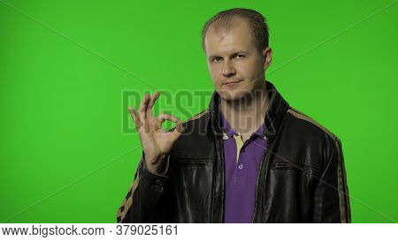 Cheerful Glad Rocker Man In Leather Jacket Showing Ok Gesture And Smiling At Camera With Optimistic