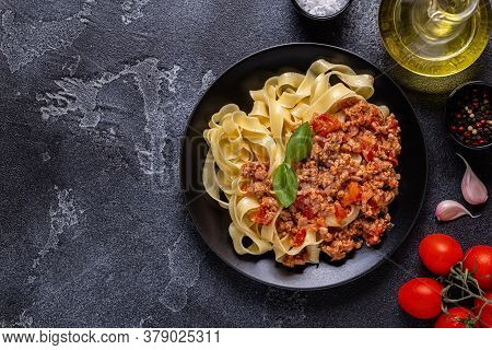 Traditional Italian Pasta Bolognese On A Black Plate.