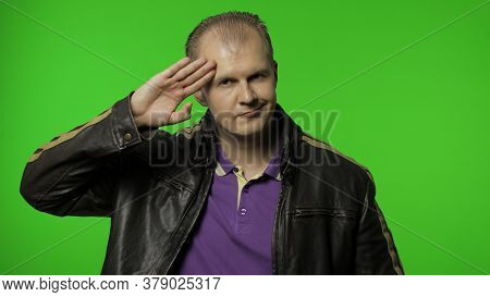 Positive Rocker Man In Leather Jacket Saluting With Hand, Saying Yes Sir And Looking At Camera With