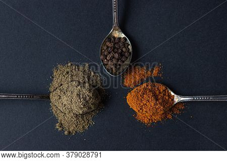 Three Different Peppers. Ground Black Pepper And Peppercorns And Red Ground Pepper Lie On A Black Ba