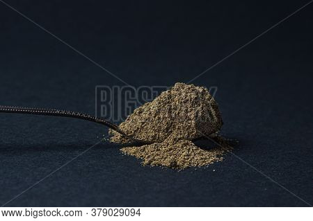 Black Ground Pepper On A Black Background. A Spoonful Of Ground Black Pepper. Spicy Seasoning
