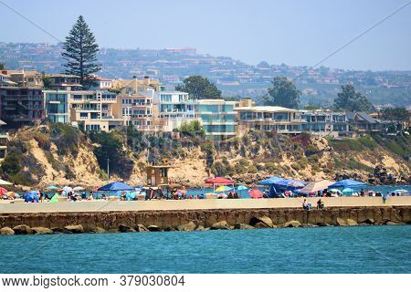 July 30, 2020 In Newport Beach, Ca:  Residential Homes On Bluffs Overlooking The Beach With Crowds O