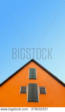 Orange House Isolated On A Blue Sky. German Home With Orange Walls And Timber Shutters. Minimalist I