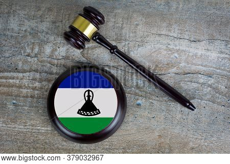 Wooden Judgement Or Auction Mallet With Of Lesotho Flag. Conceptual Image.