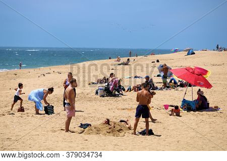 July 30, 2020 In Newport Beach, Ca:  People Sunbathing On The Beach And Swimming At The Ocean Taken