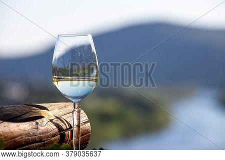 Filled Wine Glass Next To Wooden Beam And Defocused Moselle Valley In Background