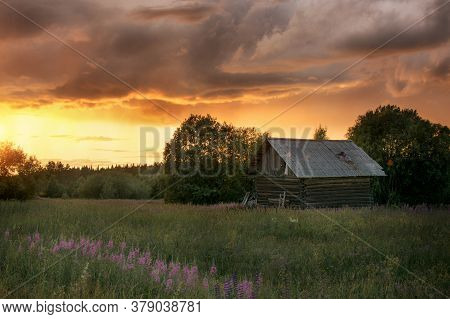 Rural Landscape. Against The Backdrop Of The Golden Setting Sun And Huge Leaden Clouds There Is A Sm