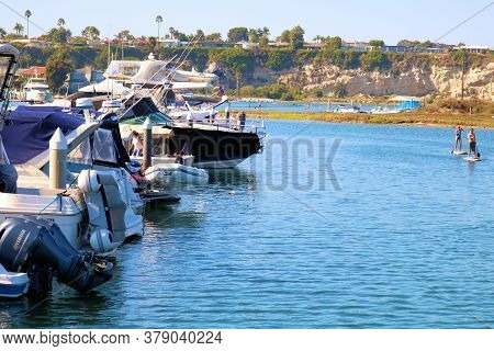 July 31, 2020 In Newport Beach, Ca:  Yachts Docked And People Paddle Boarding At The Newport Harbor