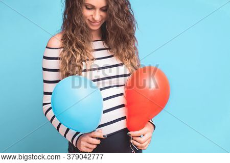 Pregnant Woman Tries To Guess The Boy Or Girl. Balloons As Symbol Of Boy And Girl. Gender Of The Unb