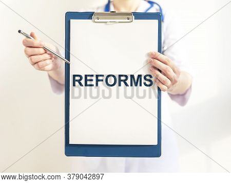 Health Care Reform Concept. Reforms Word Inscription On Paper Board In Doctor Hands