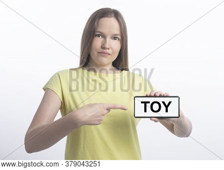 Toy Word Inscription On White Phone Screen In Female Hand. Young Caucasian Woman Holding Smartphone