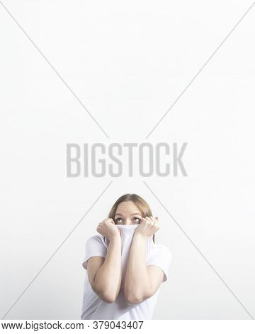 Frightened And Stressed Surprised Young Caucasian Woman Hiding In Her White T-shirt Over White Backg