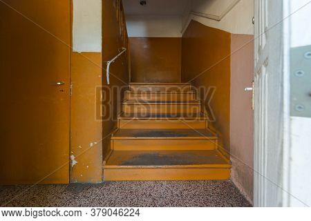 Old Dilapidated Staircase In An Old Apartment Building. Wooden Stairs, Railings And Walls Are Painte