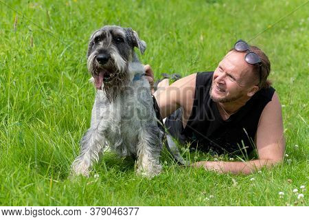 Senior Man And His Dog Lying On The Grass In The Park.