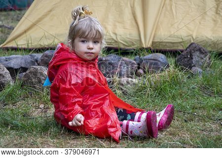 A Little Girl In A Red Raincoat With A Hood Sits On The Grass After The Rain Near A Campfire And A T