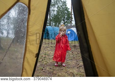 A Little Girl In A Red Raincoat With A Hood Eats Candy On A Stick In The Forest, A View From A Touri