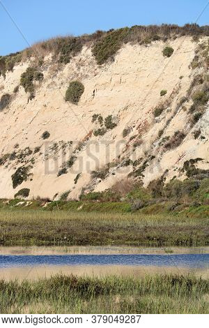 River Surrounded By Tallgrasses And A Sandstone Bluff Beyond Taken On An Estuary At Newport Back Bay