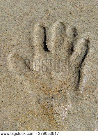Close Up On Hand Print On Beach Sand