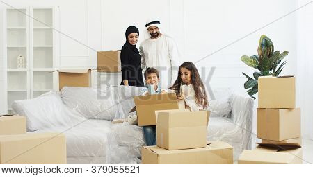 Happy Arabian Parents Bringing Stuff In Room And Small Cute Kids Unpacking Carton Boxes. Family With