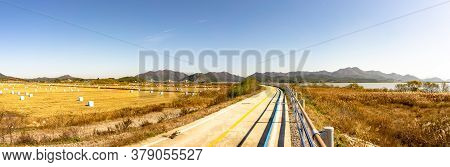 Korean Bicycle Path Pass Through The Field Full Of Straw Bales And The Yeongsan Gang River In Mokpo,