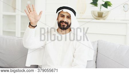 Portrait Of Handsome Young Arabian Man In Kandura Blogger Sitting On Sofa In Room And Talking To Cam