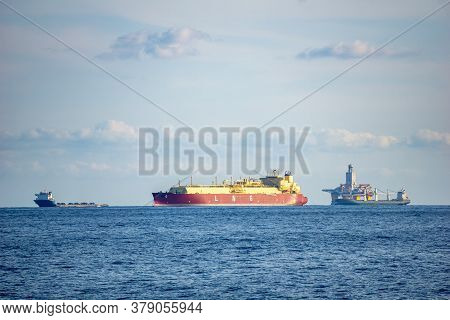 Large Liquefied Natural Gas (lng) Carrier Anchors In The Sea With Other Types Of Vessels.