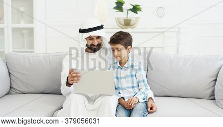 Muslim Father In Kandura Sitting On Couch In Living Room With Small Cute Son Using Laptop And Talkin