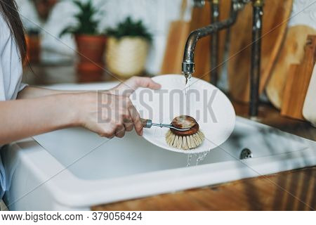 Young Woman Washes Dishes With Wooden Brush With Natural Bristles At Window In The Kitchen. Zero Was