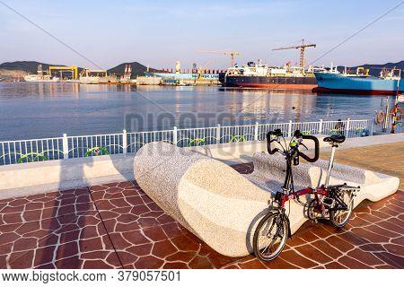 Geoje, South Korea - June 15, 2017: Brompton Folding Bike Parks On The Street Across Dsme Shipbuilde
