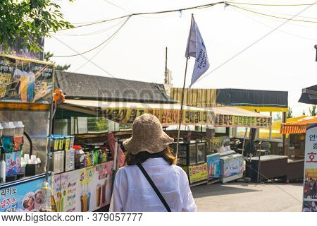 Busan, South Korea - July 20, 2017 : Local Guide With Guided Flag  Leads The Group Of Tourist Walk T