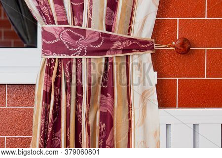 A Curtain, An Element Of A Curtain In A Room Tied With A Ribbon Against A Red Brick Wall And Window.