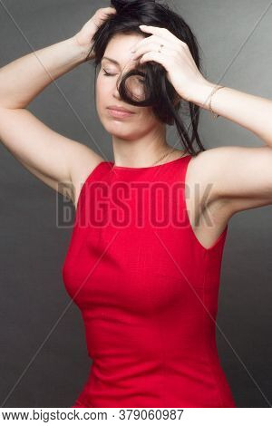 Portrait Of A Brunette On A Gray Studio Background In A Red Dress