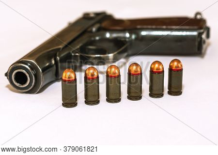 Six Combat Pistol Cartridges Of Calliber 9 Mm Stand In Front Of A Pistol On A White Background Side
