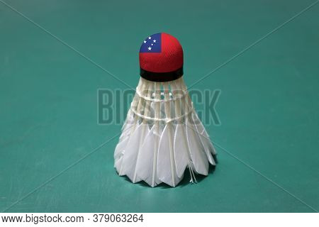 Used Shuttlecock And On Head Painted With Samoa Flag Put Vertical On Green Floor Of Badminton Court.