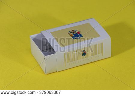 New Jersey Flag On White Box With Barcode And The Color Of State Flag On Yellow Background, Paper Pa