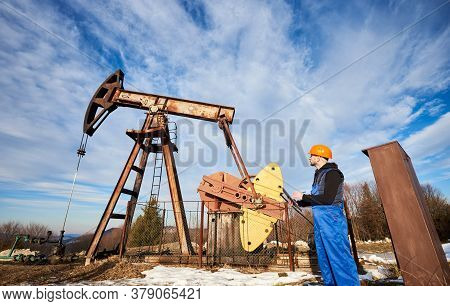 Petroleum Engineer In Work Overalls And Helmet Holding Clipboard, Checking Oil Pumping Unit, Making