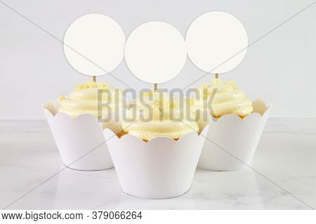 Three French Vanilla Cupcakes Sitting Happily In Scalloped Cupcake Liners Atop A Classy White Marble