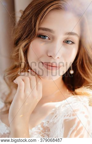 Close-up. The Sun Glare. Portrait Of A Beautiful Young Girl With Long Hair In White Dress.