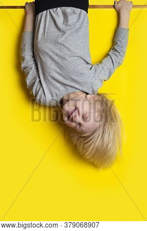 Funny Fair-haired Boy Hanging Upside Down On Yellow Background And Grimace. Vertical Frame.