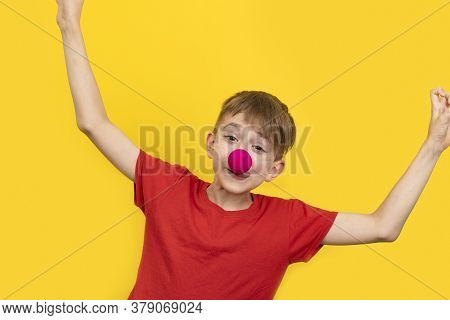Cheerful Clown Kid Child. April Fools Day. Child With Red Clown Nose On Yellow Background