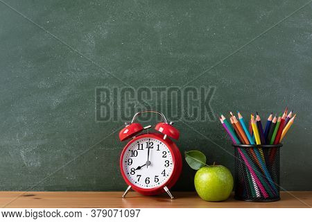 Education And Back To School Template With Alarm Clock, Green Apple And Colorful Pencils Against Bla