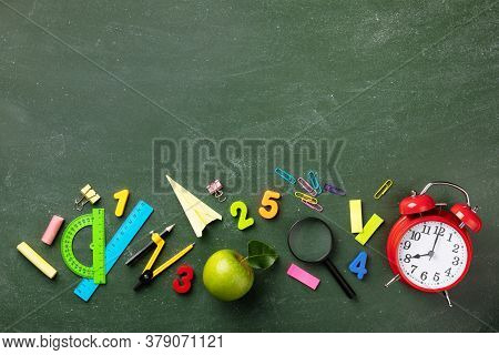 Back To School And Education Concept With Alarm Clock, School Supplies And Green Apple On Blackboard