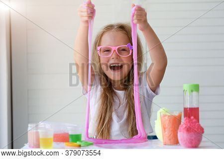 A Little Girl With Glasses Is Played With A Homemade Pink Slime. Kids Hands Playing Slime Toy.