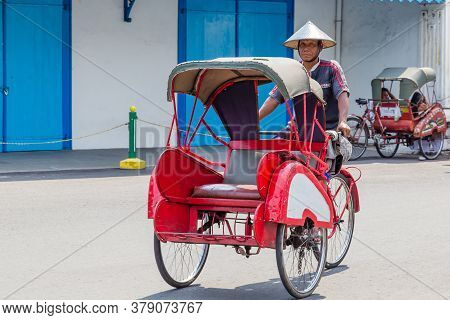 Solo, Indonesia - November, 02, 2017 Bicyvle Taxi In Front Of The Colorfull Blue Palace Of The Sulta