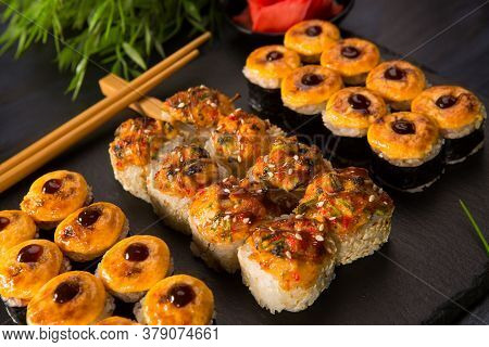 Set Of Baked Sushi Rolls With Wasabi And Ginger On Black Background. Japanese Oriental Cuisine