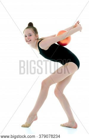 A Charming Little Girl Is Engaged In Fitness With A Ball. The Concept Of Gymnastics, Health And Spor