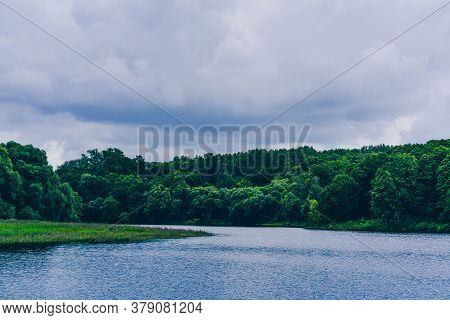 Calm Pond In Green Countryside. Above Amazing Lake With Tranquil Water Located Near Green Forest In
