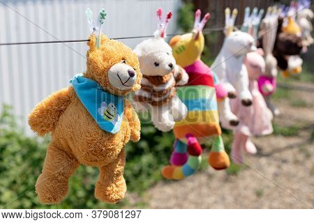 Various Plush Toys Hanging From The Clothesline In The Backyard On A Sunny Summer Day. Disinfection