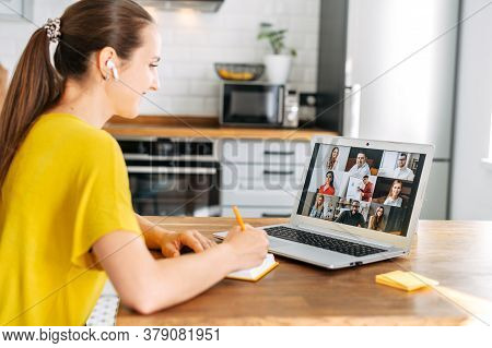 Side View Of Young Woman Watching On Laptop Display With A Group Of Multiracial People On It And Wri