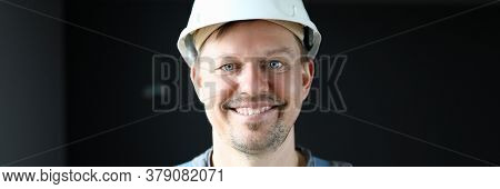 Man In Work Clothes In Protective Helmet Smiling. Providing Additional Protection Against Mechanical